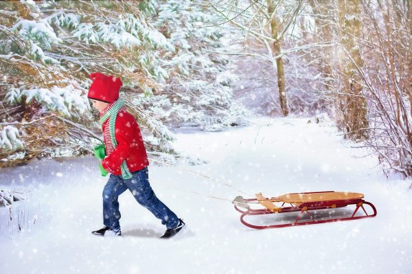 Young boy pulling a sled in a winter wonderland.